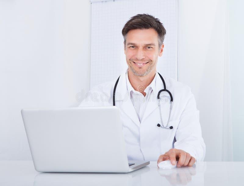 Doctor que usa la computadora portátil fotos de archivo libres de regalías