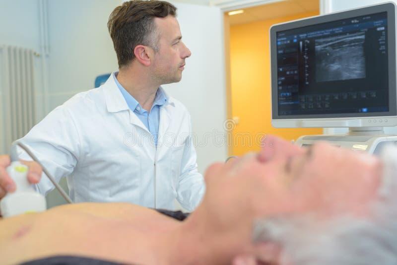 Doctor que usa la exploración del ultrasonido en mayor-varón-paciente del abdomen en clínica imagenes de archivo