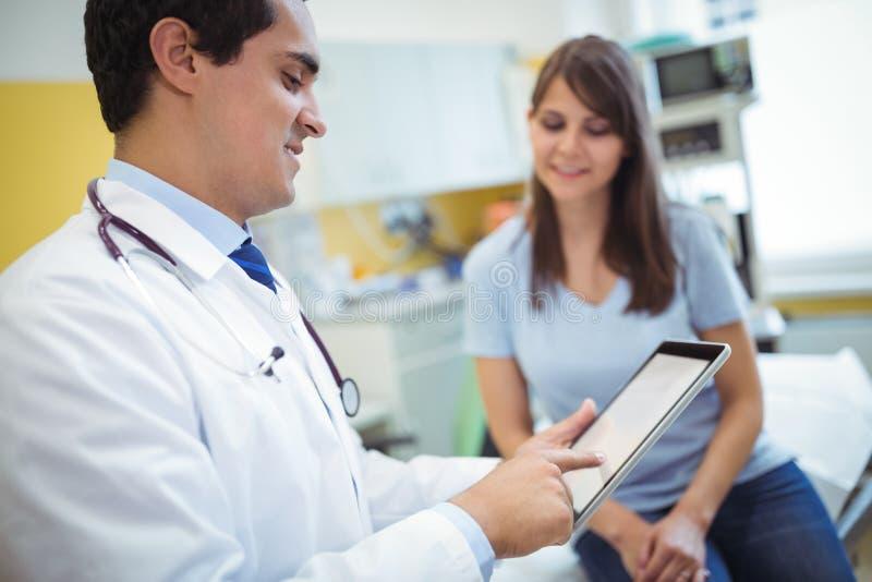 Doctor que usa la tableta digital mientras que consulta al paciente fotos de archivo