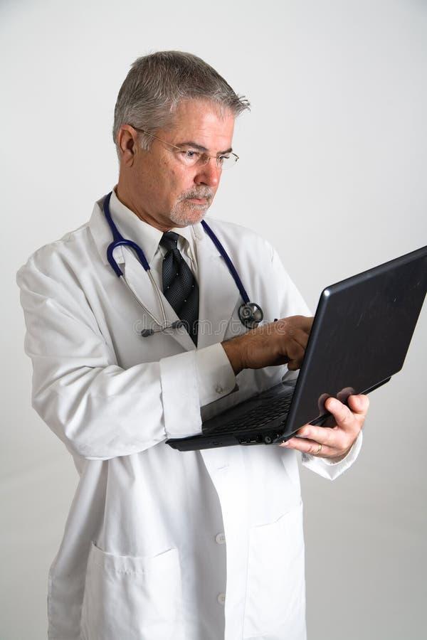 Doctor que usa vertical del ordenador imágenes de archivo libres de regalías