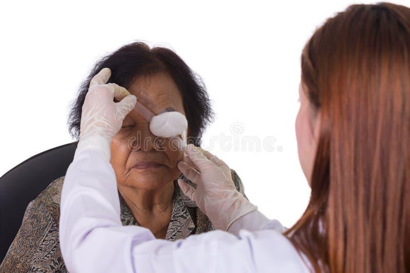 Doctor que venda el ojo del paciente imagenes de archivo
