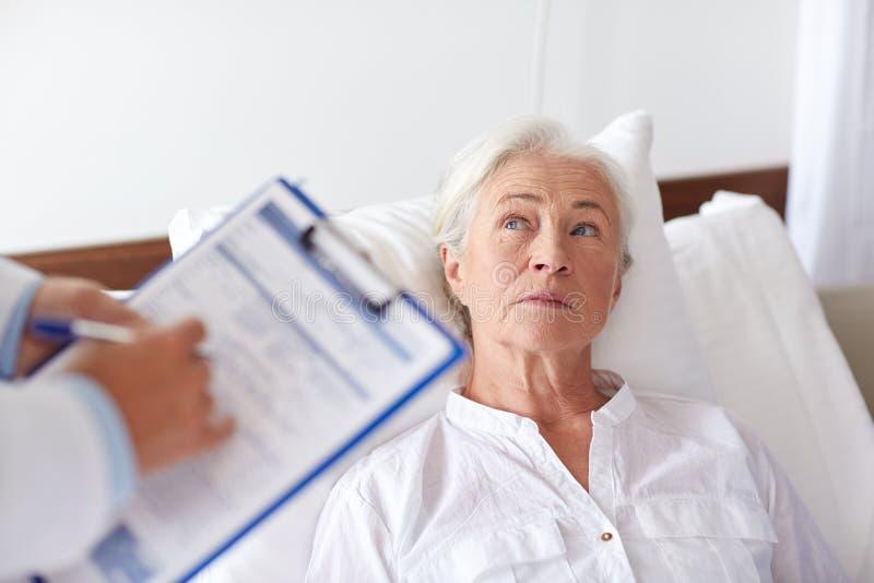 Doctor que visita al paciente mayor de la mujer en el hospital imagen de archivo