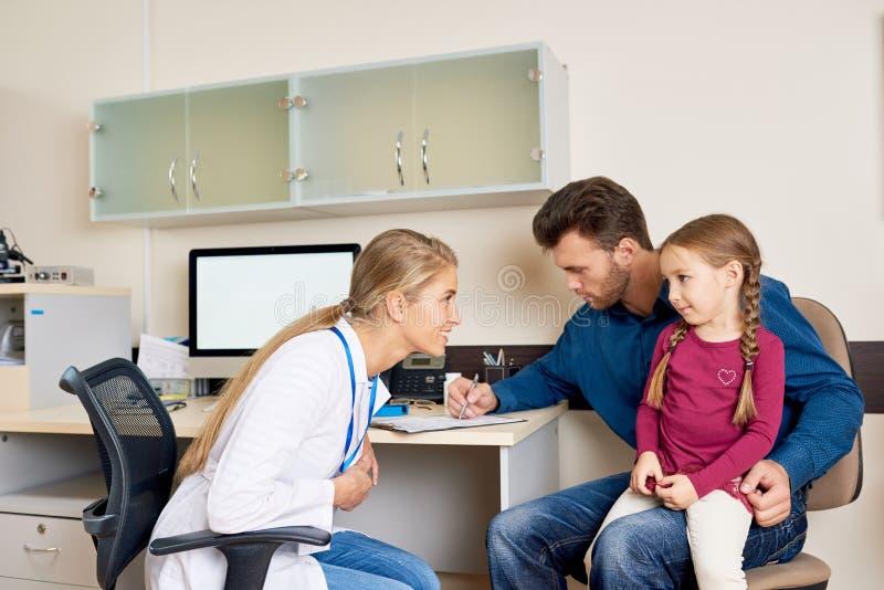 Doctor que visita del padre y de la hija foto de archivo
