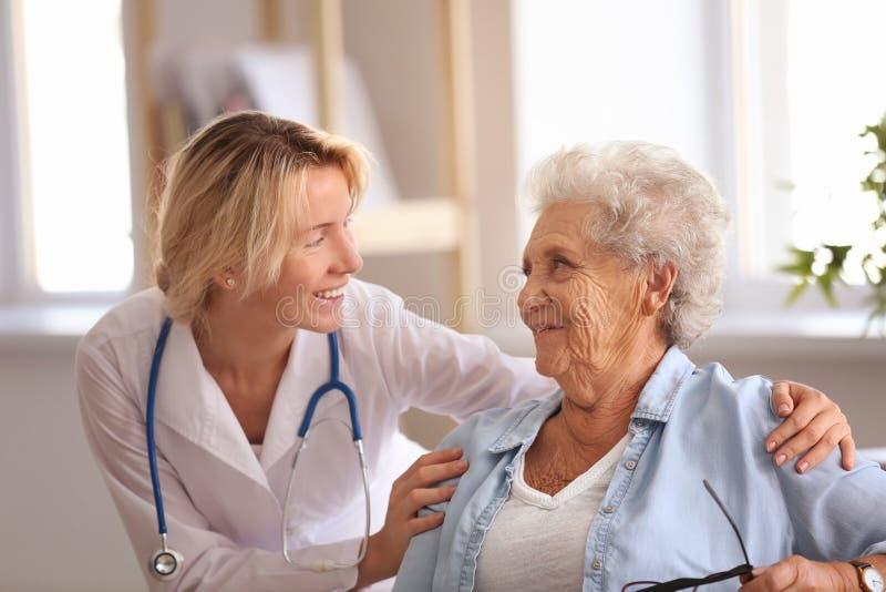 Doctor que visita a la mujer mayor en casa imagenes de archivo