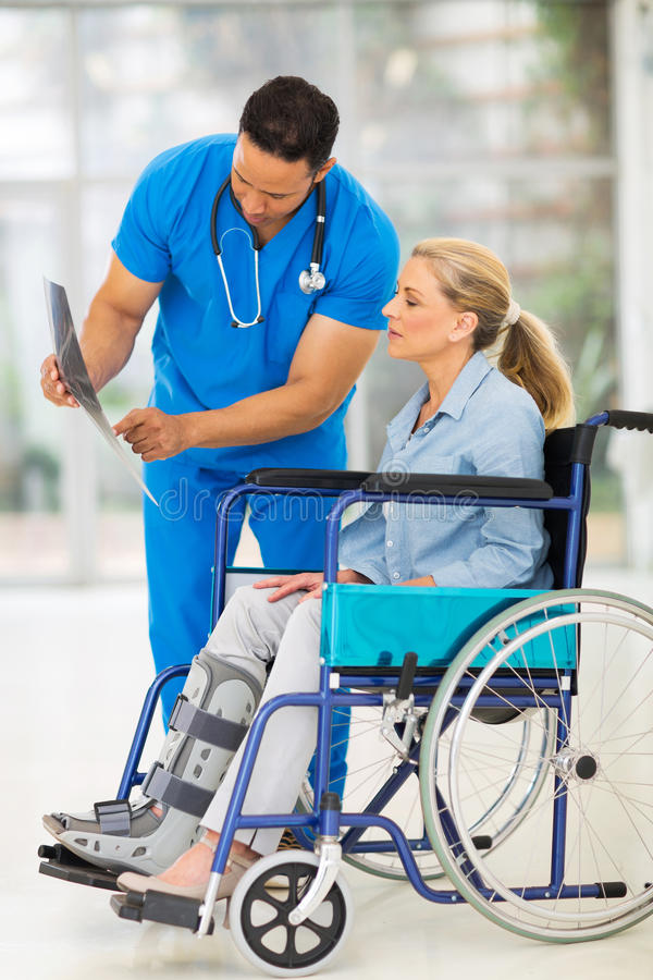 Doctor x-ray patient. Doctor explaining x-ray results to patient in wheelchair royalty free stock photos