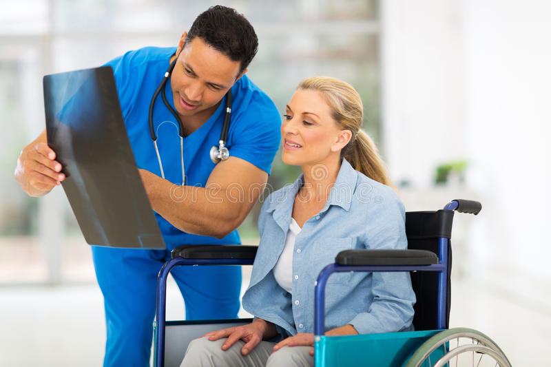 Doctor x-ray senior patient. Male doctor showing x-ray report to senior disabled patient in hospital stock photo
