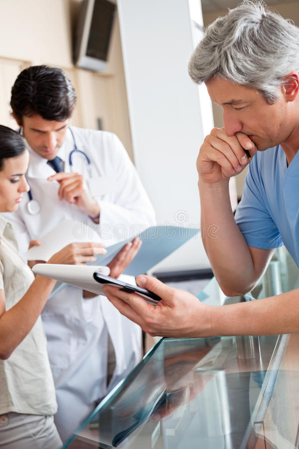 Doctor Reading Document At Reception. Mature male doctor reading document while colleagues standing at reception stock photo