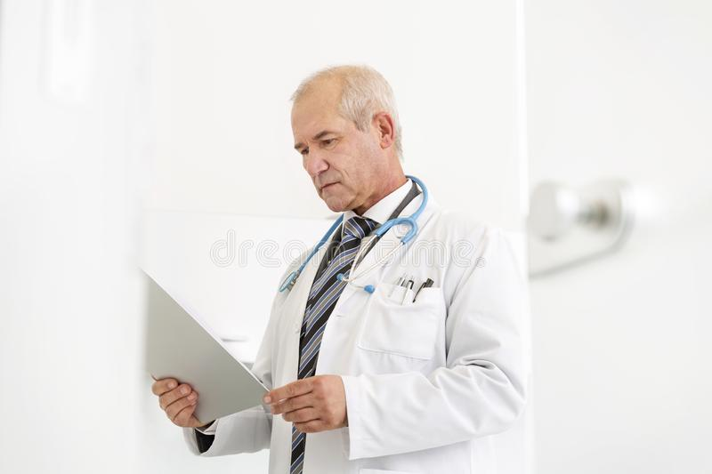 Doctor reading medical report on clipboard at dental clinic stock photo