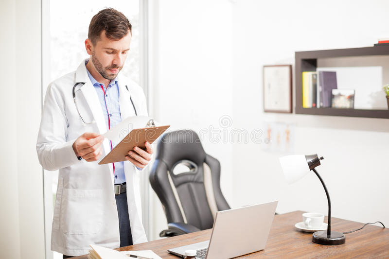 Doctor reading a patient's history in an office. Handsome young doctor with a lab coat and stethoscope reading a patient's history while standing in his office stock images
