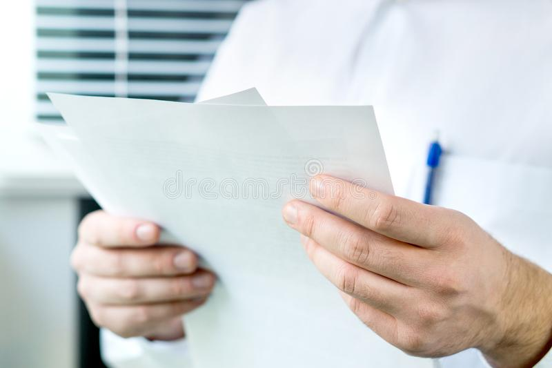 Doctor reading patient`s medical record from paper in hospital. stock images