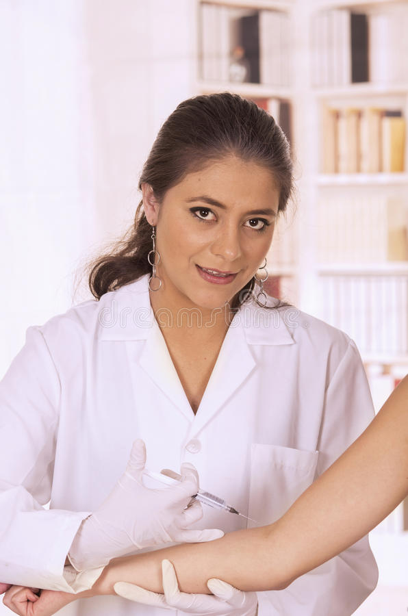 Doctor ready with injection holding patients arm. Doctor injecting needle injection holding patients arm on white stock image