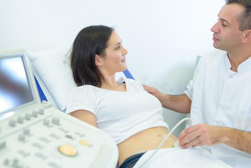 Doctor reassuring patient while performing ultrasound. Ultrasound royalty free stock photos