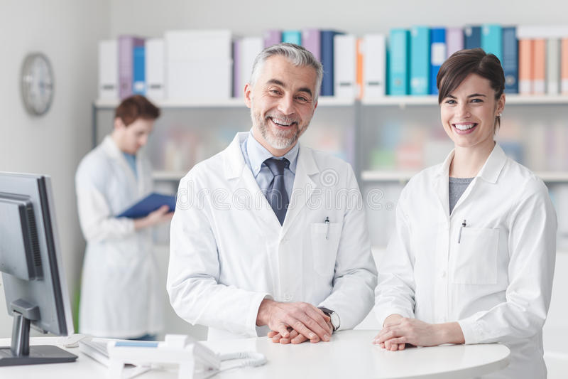 Doctor at the reception desk with his assistant. They are smiling at camera, healthcare and medical staff concept royalty free stock images