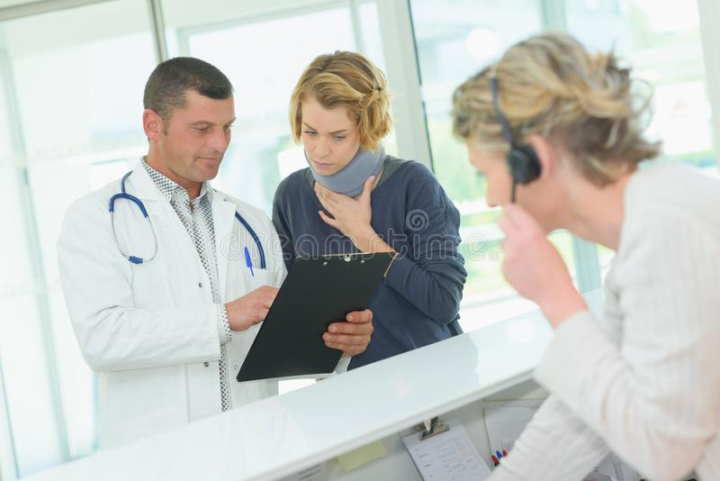 Doctor at reception desk with woman wearing neck brace stock images