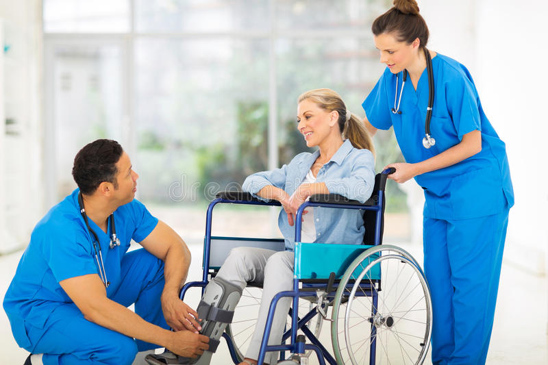 Doctor recovering patient. Friendly doctor talking to a recovering patient in wheelchair royalty free stock image