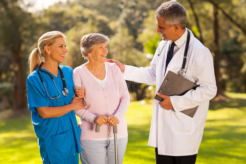 Doctor recovering senior. Caring male doctor talking to recovering senior patient outdoors in hospital garden stock images