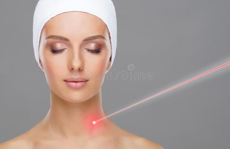Doctor removing moles using laser ray. Beauty portrait of a young woman. Birthmark removal, plastic surgery, skin stock photos