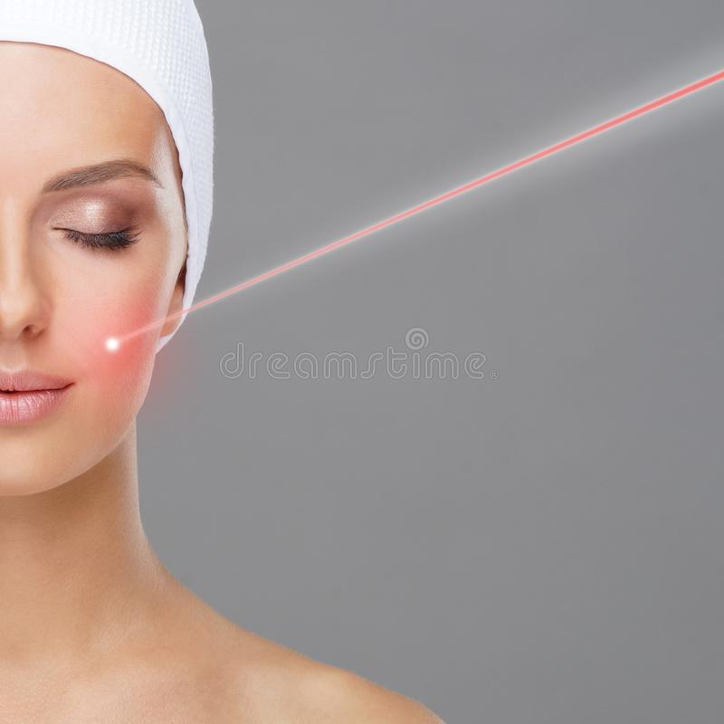 Doctor removing moles using laser ray. Beauty portrait of a young woman. Birthmark removal, plastic surgery, skin stock image