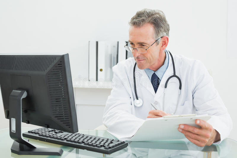 Doctor with report looking at computer monitor at medical office stock photo