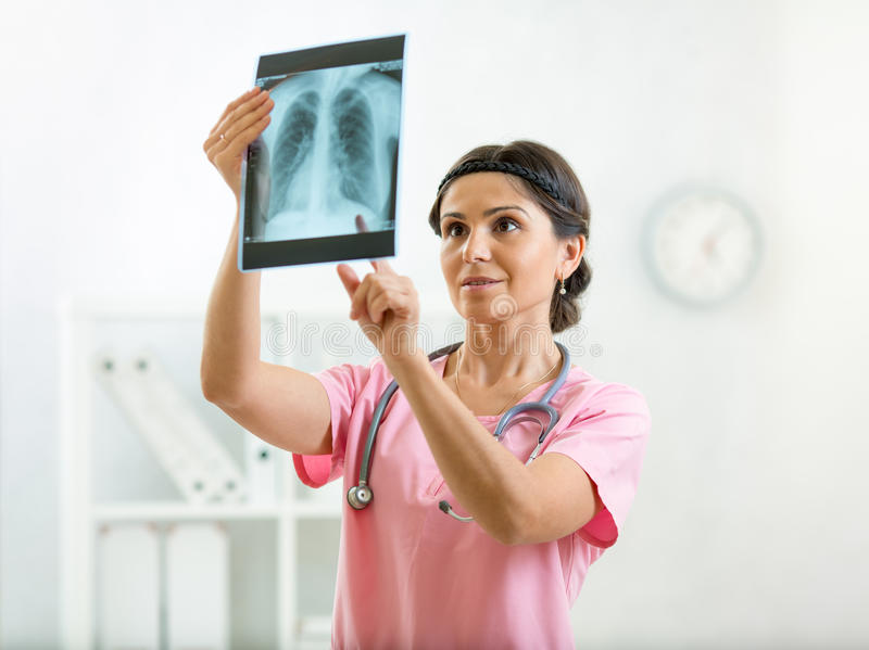 Doctor reviewing x-ray photo in office. Female doctor reviewing x-ray photo in office royalty free stock image