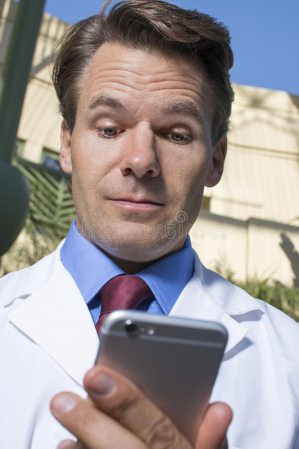 Doctor reviewing smart phone messages. Closeup low angle head shot of handsome Caucasian medical doctor in white lab coat reviewing messages on smart phone stock photo