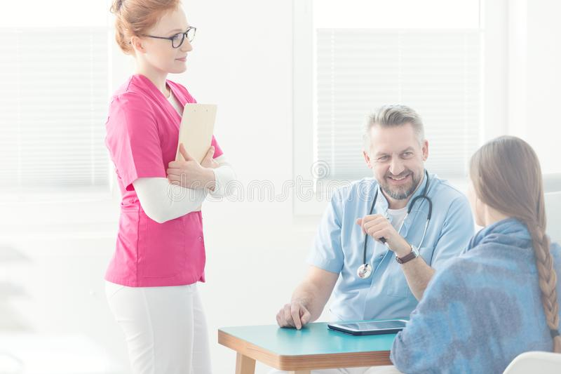 Doctor`s assistant during medical interview. Doctor`s assistant in pink uniform next to a general practitioner during medical interview royalty free stock photo