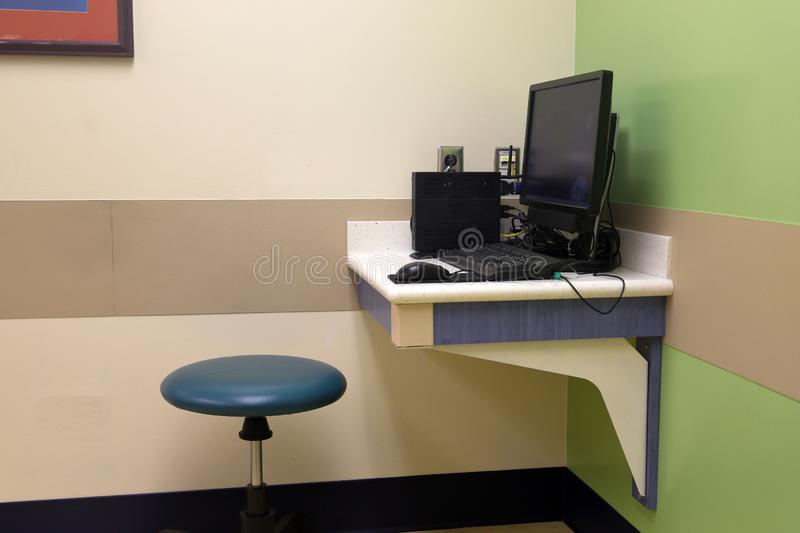 Doctor`s computer desk in medical exam room royalty free stock image