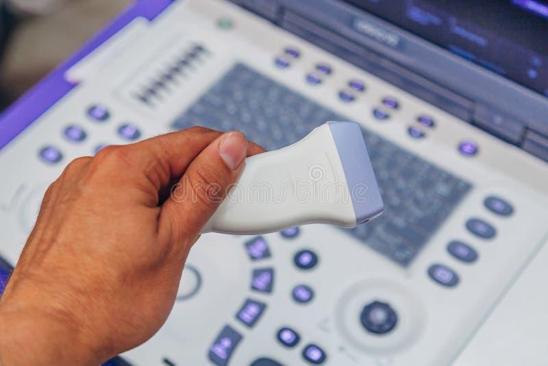 Doctor`s hand holding ultrasound probe of ultrasound scanner for medical diagnostics stock photo