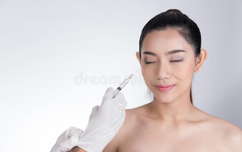 Doctor& x27;s hand making botox injection in girl& x27;s face. young asia stock photo