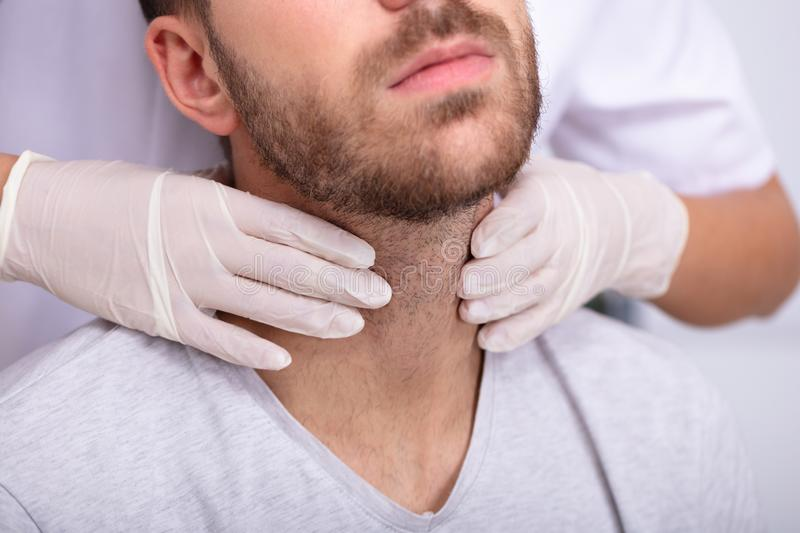 Doctor Performing Physical Exam Palpation Of The Thyroid Gland. Doctor`s Hand Wearing Gloves Performing Physical Exam Palpation Of The Thyroid Gland stock photography
