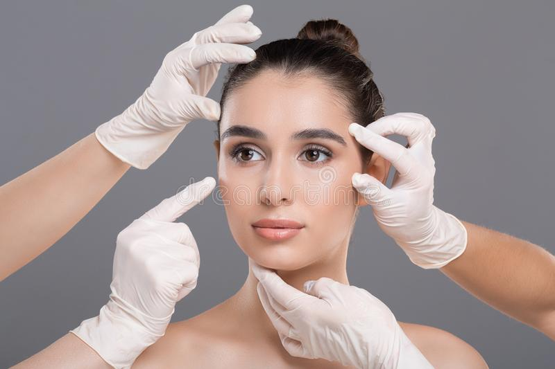 Doctor`s hands in gloves touching face of young beautiful woman. Aesthetic Cosmetology concept. Doctor`s hands in gloves touching face of young beautiful woman royalty free stock image