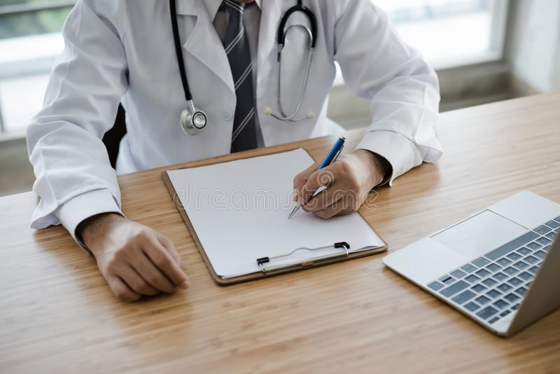 The doctor`s hands are writing at a desk. royalty free stock image