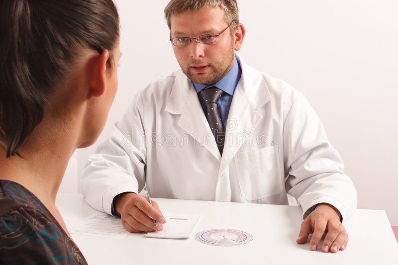 At the doctors office. Doctor explaining diagnosis to his female patient - front
