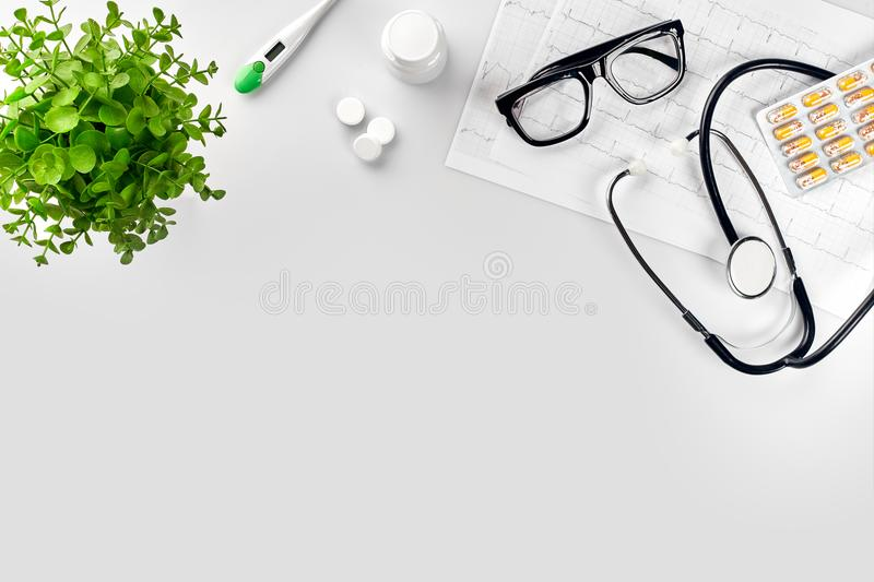 Doctor`s office desk with medical documents, charts, eyeglasses and stethoscope. Top view. Copy space. White background. Still life. Flat lay royalty free stock photography