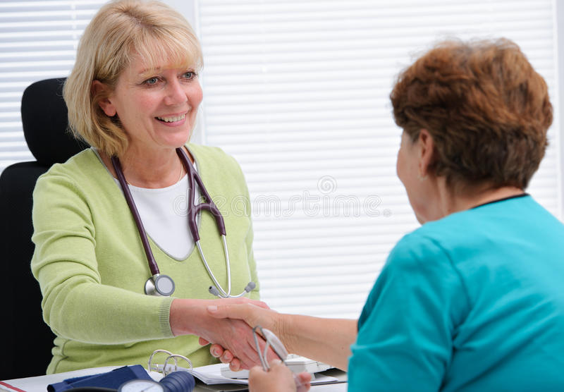At the doctor's office. Doctor shaking hands to patient in the office royalty free stock image