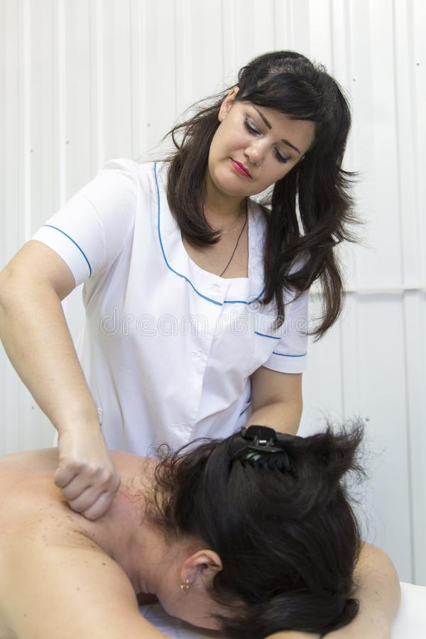 Massage of female shoulders and neck. In a doctor`s office with white walls, a women is given a massage on her neck stock images