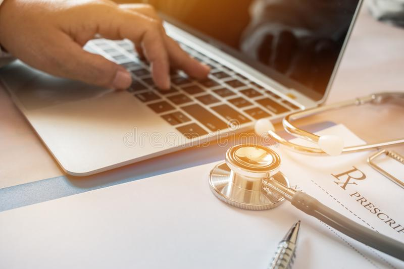 Doctor's working on laptop computer, writing prescription clipbo stock photos