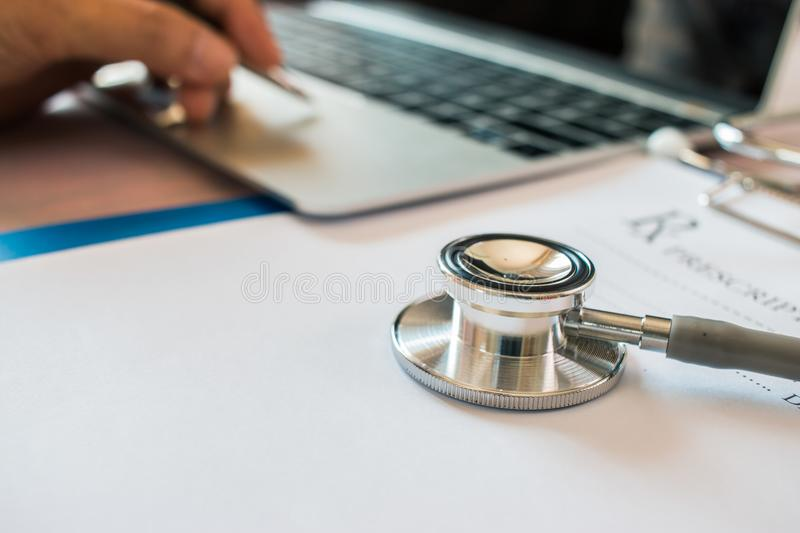 Doctor`s working on laptop computer, writing prescription clipboard with record information paper folders on desk in hospital or stock photo