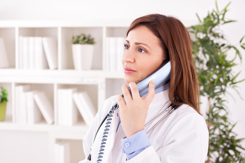 Doctor scheduling with phone. Female doctor scheduling with phone stock images