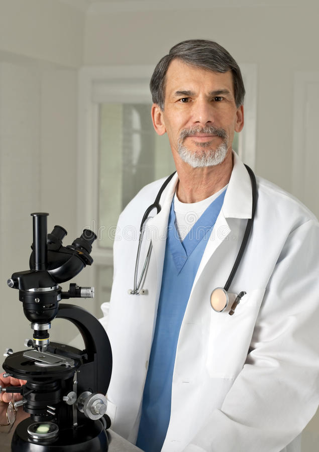 Doctor or Scientist at the Microscope. Portrait of mature doctor, scientist or chemist at the microscope stock photo
