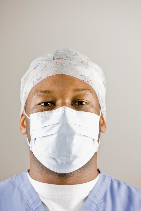 Doctor in scrubs, surgical mask and surgical cap. Doctor in sterile scrubs, surgical mask and surgical cap stock image