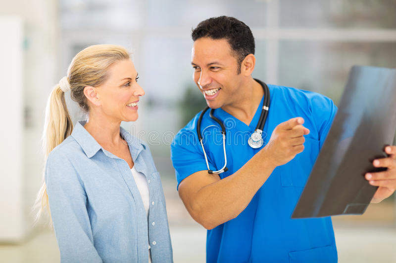 Doctor senior patient. Happy doctor and senior patient looking at x-ray result in hospital stock image