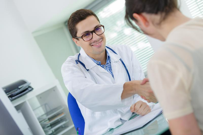 Doctor shaking hands with female patient stock images