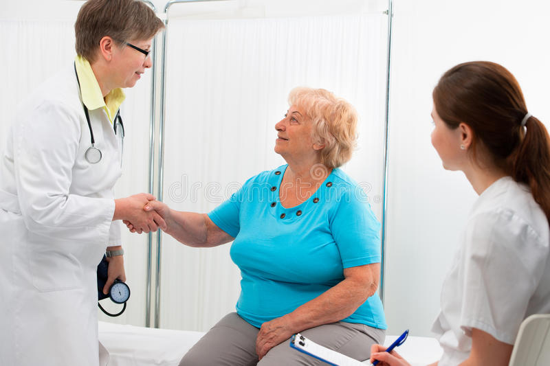 Doctor shaking hands with patient stock photography