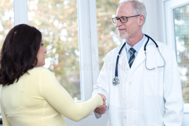 Doctor shaking hands to patient royalty free stock photography