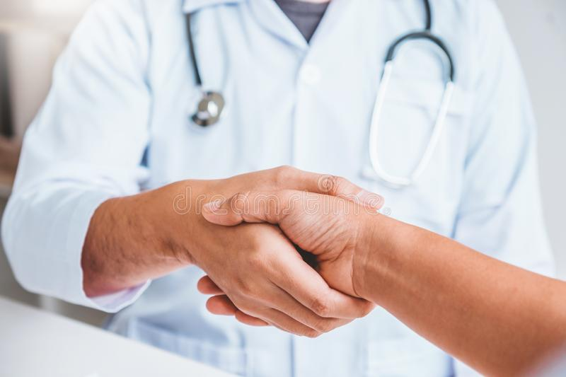 Doctor shaking hands with woman patients at hospital office stock photo