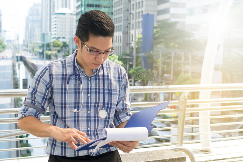 Doctor in the shirt with stethoscope writing the patient chart. At city background stock photography