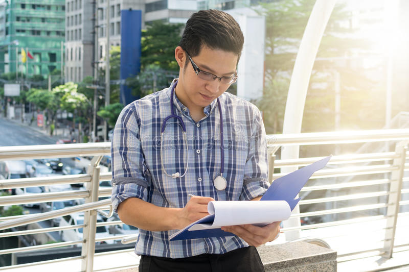 Doctor in the shirt with stethoscope writing the patient chart. At city background stock photo