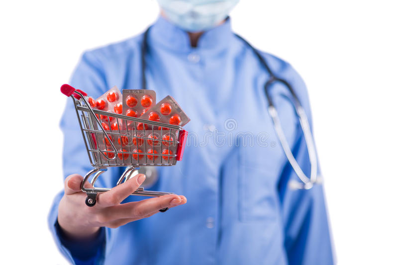 The doctor with shopping cart full of pills isolated on white. Doctor with shopping cart full of pills isolated on white royalty free stock photos