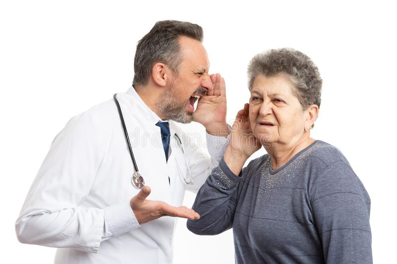 Doctor shouting in deaf patient ear royalty free stock photography